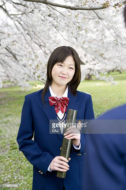 High School Students Under Cherry Blossoms with Holding Diploma