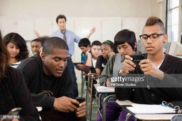 High school students using cell phones in classroom