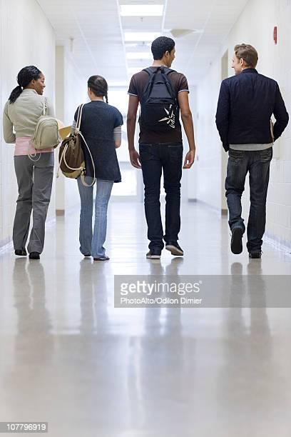 High school students walking down school corridor, rear view