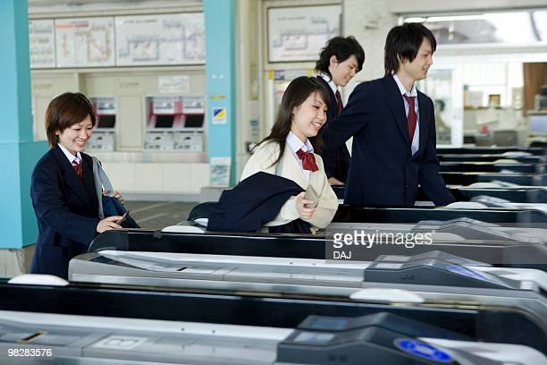 high school students walking through automatic ticket wicket at station - 改札 ストックフォトと画像