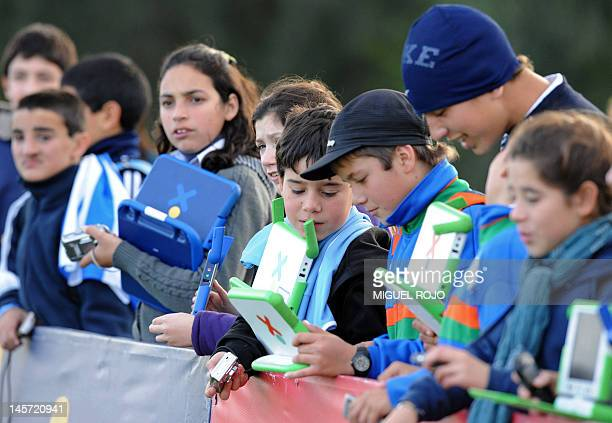 High school students with their XO laptops of the 'One Laptop per Child' program and school children with theirs watch a training session of the...