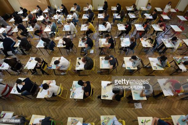 High school students work on a 4 hours philosophy dissertation, that kicks off the French general baccalaureat exam for getting into university, on...