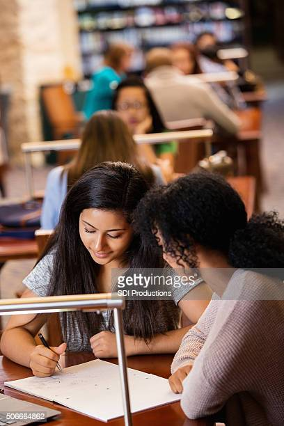 high school study groups doing homework in crowded library - incidental people stock pictures, royalty-free photos & images