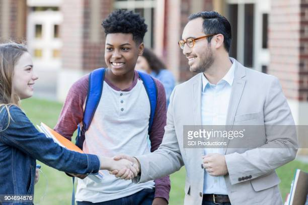 Middelbare schoolleraar feliciteert student