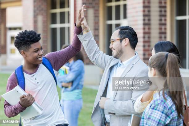 high school teacher gives student a high five - teacher stock pictures, royalty-free photos & images