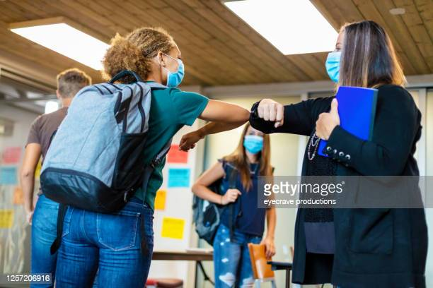 high school teacher greeting student with elbow bump and all wearing face masks in classroom setting - teenagers only stock pictures, royalty-free photos & images