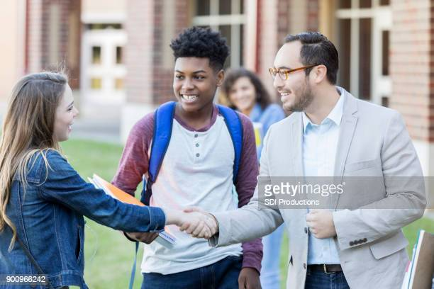 high school teacher shaking hands with new teen student outdoors. - college professor stock photos and pictures