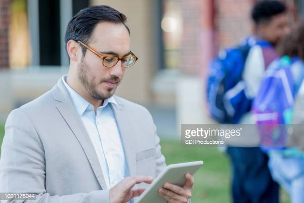 high school teacher using digital tablet - school principal stock pictures, royalty-free photos & images
