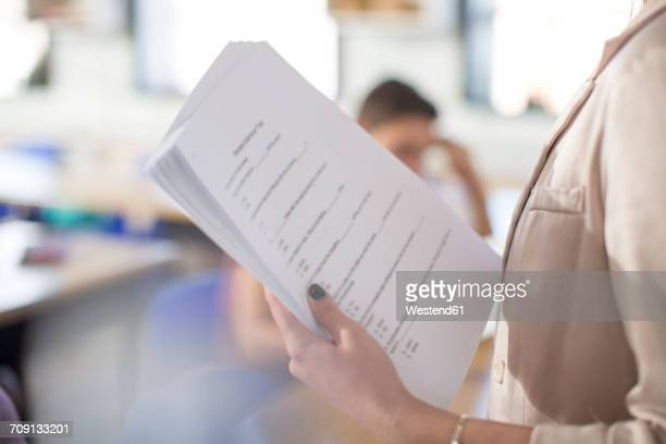 High school teacher with test notes in classroom