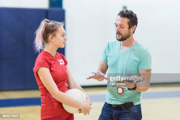high school volleyball coach talking to one of his players - high school volleyball stock photos and pictures