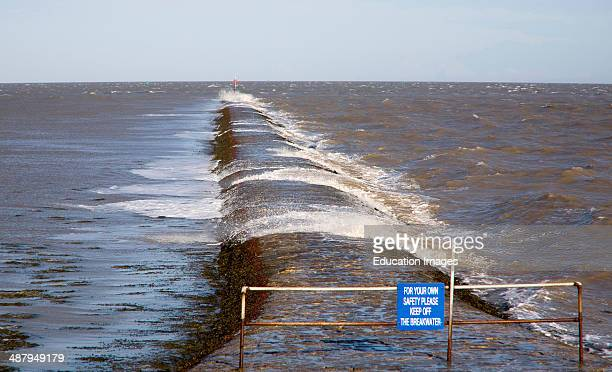 High seas forcing waves over the harbor mouth breakwater at Harwich Essex England