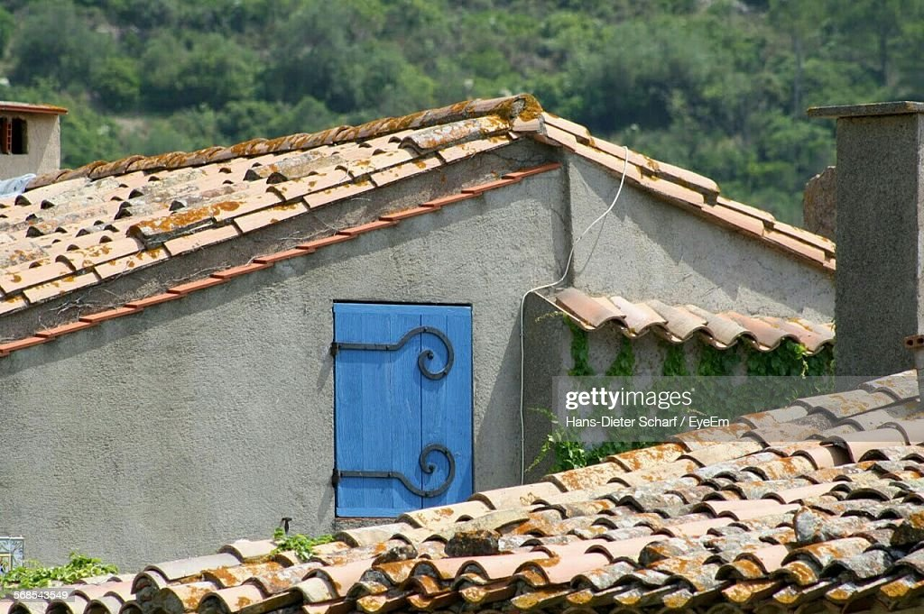 High Section Of House With Tiled Roof Against Trees : Stock Photo