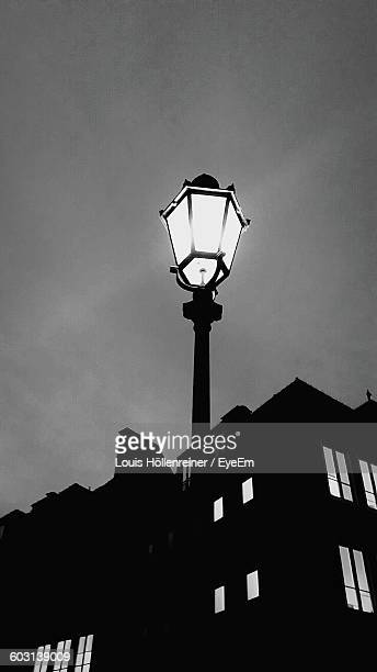 High Section Of Lamp Post Against Silhouette Built Structure