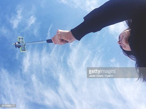High Section Of Woman Taking Selfie Against Sky