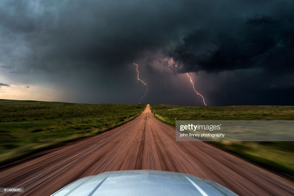 High speed storm chasing, taken from the roof of a moving car off road with double lightning bolts ahead. Colorado, USA. : Stock Photo