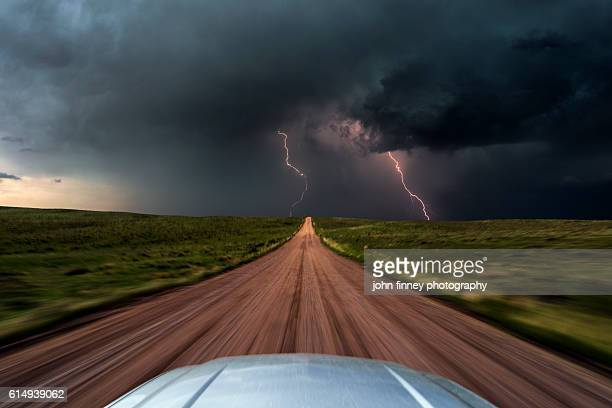 High speed storm chasing, taken from the roof of a moving car off road with double lightning bolts ahead. Colorado, USA.