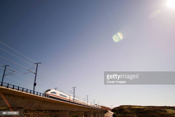 high speed train on railway bridge against clear sky - high speed train stock pictures, royalty-free photos & images