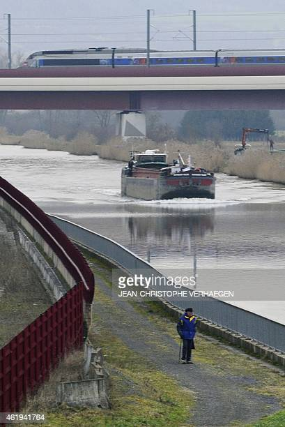A TGV high speed train passes over a bridge near a barge on the lateral canal of the Moselle river in Vandieres northeastern France on January 22...