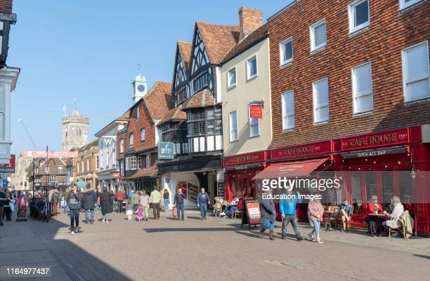 High Street, Salisbury, Wiltshire, England UK, Shoppers on the High Street close to the entrance to Old George Mall Church tower of St Thomas and St...