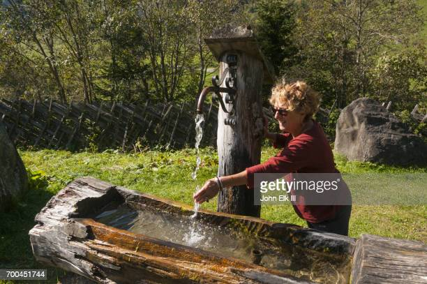 High Tauern landscape with fountain and woman