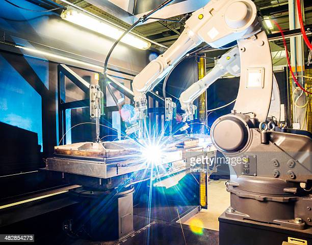 high tech robotic welder in modern metal factory - automation stock pictures, royalty-free photos & images