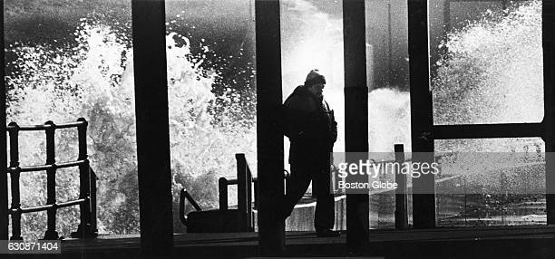 High tide caused by a full moon and high winds the day before sends waves over Nantasket Beach seawall in Hull Mass as a pedestrian moves away on Jan...