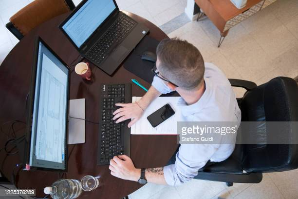 High view of a young man programmer and websites manager while working at home on May 16, 2020 in Turin, Italy. During the Lockdown of the...