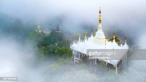 high view of khao na nai luang temple with the mist in the morning at surat thani province, southern of thailand - surat thani province stock pictures, royalty-free photos & images