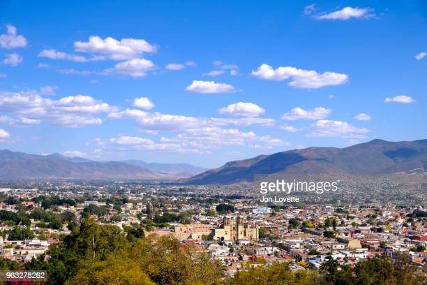 high view of skyline of oaxaca city with surrounding mountains and santo domingo church - oaxaca stock pictures, royalty-free photos & images