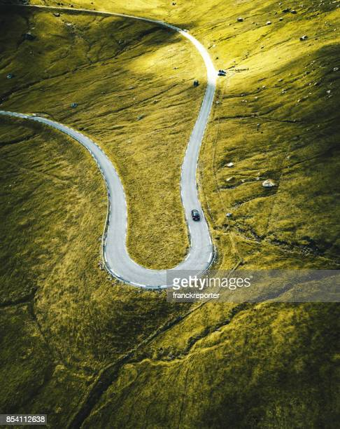 high view of the winding roads at the faroe islands - mountain road stock pictures, royalty-free photos & images