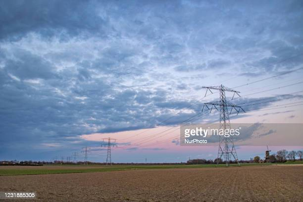 High voltage electricity poles during magic hour. The metal towers as seen in the sunset in the Dutch countryside distribute electric energy from the...
