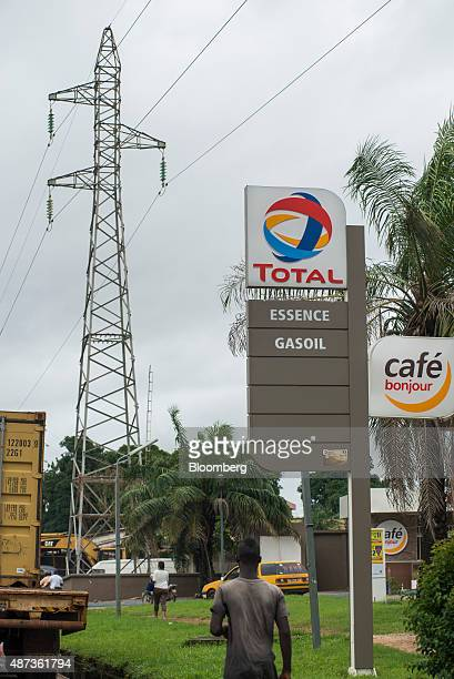 High voltage electricity power lines hang from a pylon above a gas station operated by Total SA in Conakry Guinea on Saturday Sept 5 2015 While...