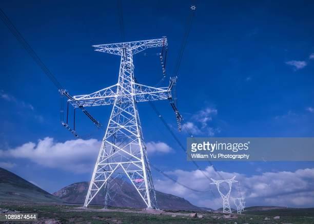 high voltage power transmission towers and lines - inviare foto e immagini stock