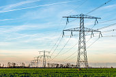 High voltage towers with thick hanging power cables in a rural landscape in the Netherlands