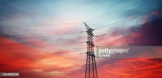 high voltage transmission tower at sunset - power supply stock pictures, royalty-free photos & images