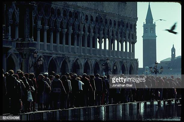 High water forces Venice residents to use a temporary bridge to cross St Mark's Square