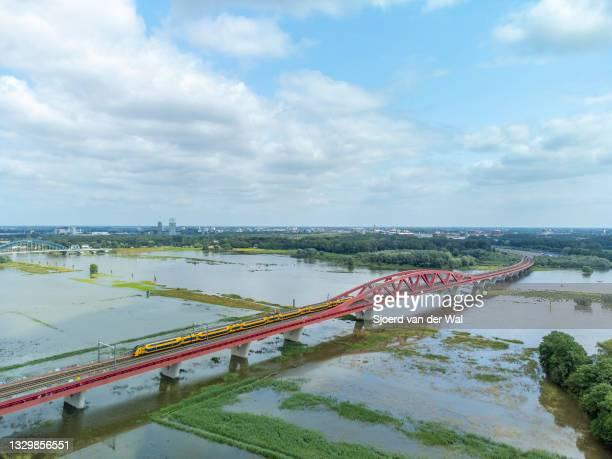 High water level on the floodplains of the river IJssel at the Hanzeboog train bridge with a train of the Dutch railways Nederlandse Spoorwegen...