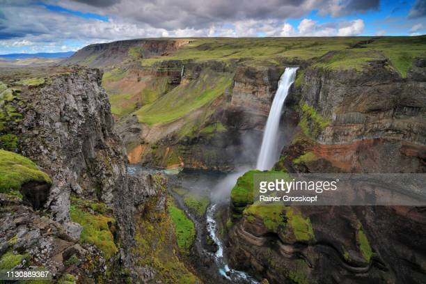 A high waterfall flows into a magnificent canyon in the mountains