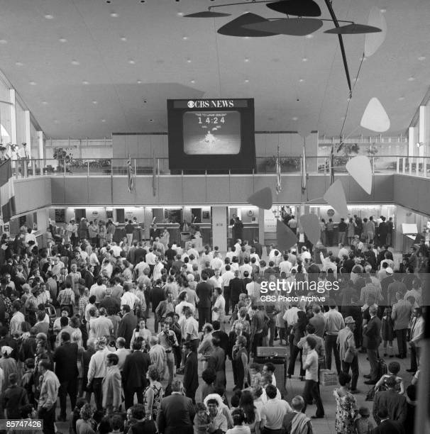 High-angle interior view of the International Arrival Building at John F. Kennedy International Airport shows a crowd of passengers as they stand...
