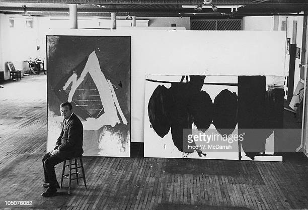 Highangle portrait of American abstract expressionist Robert Motherwell as he sits on a stool next to several of his paintings in a loft on East 86th...