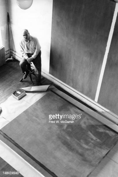 Highangle portrait of American artist Barnett Newman as he sits on a stool in his studio New York New York April 2 1961