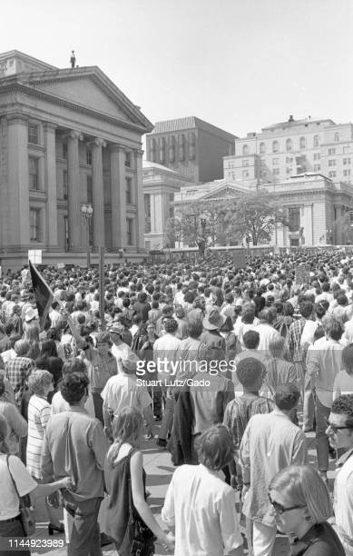 High-angle shot of a crowd of protestors filling the street in front of a column-fronted building, with policemen on its roof, during the Kent...