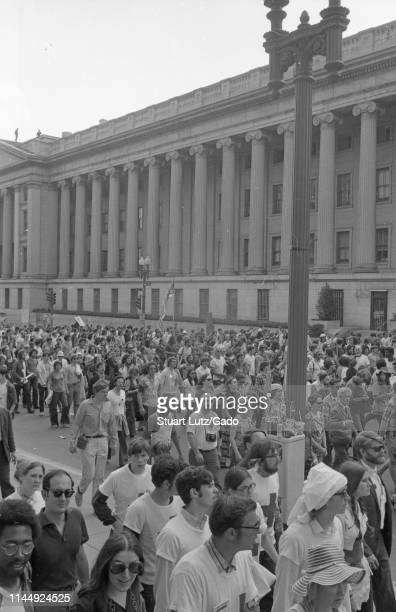 High-angle shot of a crowd of protestors walking in the street in front of a large building during the Kent State/Cambodia Incursion Protest,...