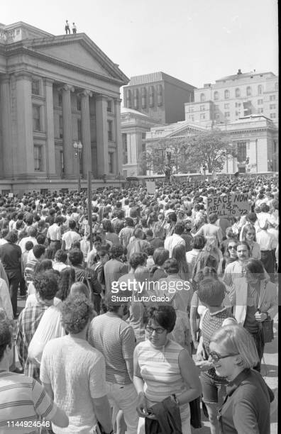 High-angle shot of a large crowd of protestors filling the street in front of a column-fronted building, with policemen on its roof, during the Kent...