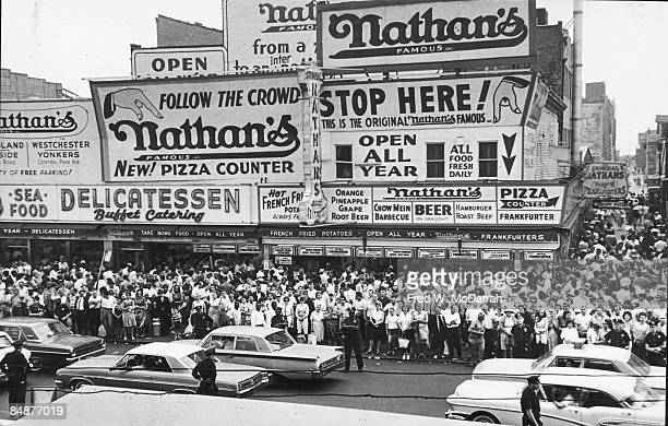 Highangle view of a large crowd of people gathered on the sidewalk in front of Nathan's Famous a fast food restaurant for a rally in support of John...