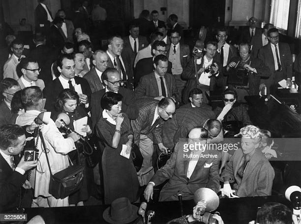Highangle view of American actor Lana Turner seated in a courtroom surrounded by reporters at the trial of her daughter Cheryl Crane for the murder...