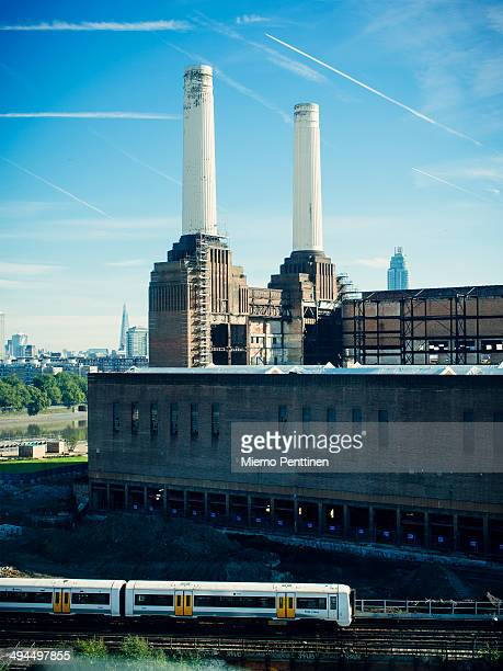 CONTENT] A highangle view of Battersea Power Plant on a sunny autumn day with a train running on a railroad track in the foreground