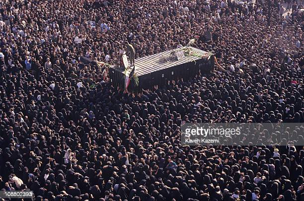 Highangle view of crowds of mourners as they surround the transport container used to move the body of Ayatollah Khomeini to a burial site Tehran...