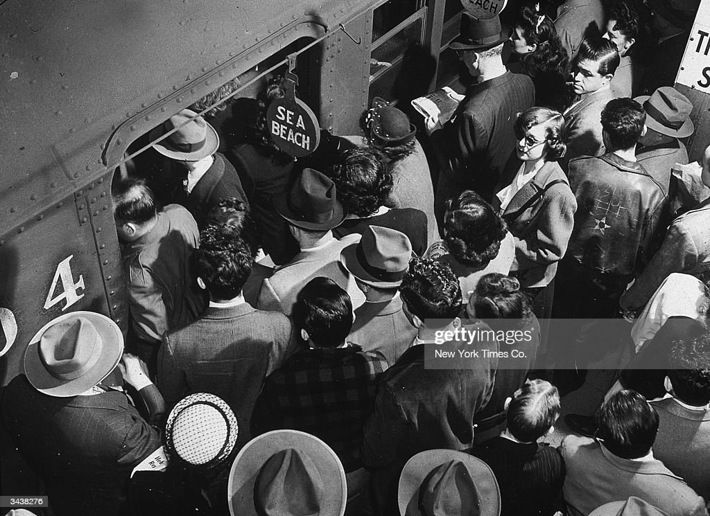 High-angle view of rush hour passengers boarding the Sea Beach subway train from a crowded platform at Times Square in New York City.