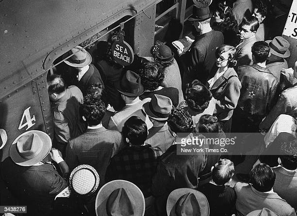 Highangle view of rush hour passengers boarding the Sea Beach subway train from a crowded platform at Times Square in New York City